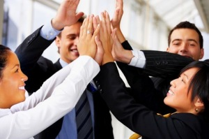 High five - Teamwork and team spirit - multi-ethnic pile of hands in the air
